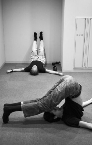 Two musians of The deutsche Kammerphilharmonie Bremen doing streching exercises on the floor before the concert in the Tokyo Opera City Concert Hall, Tokyo, Japan 16.7.2007, The deutsche Kammerphilharmonie Bremen on tour through Japan. (In Tune – Variations on an Orchestra)