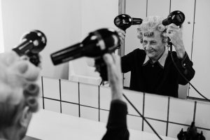 An old ladies drying her hair with 2 hairdryers in the wardrobe of the public swimming pool Vesturbaejarlaug, REykjavik, Iceland, 17.5.2015 (Water Matters)